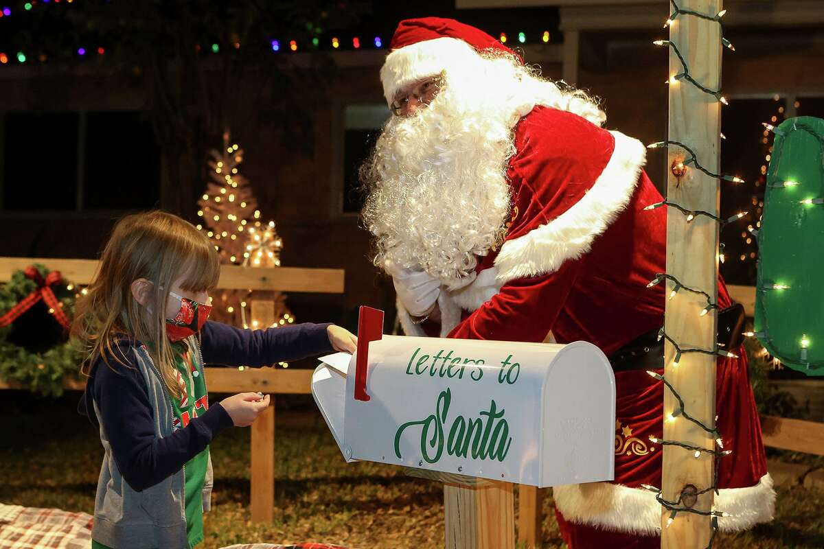 Sue Lundschen, 6, drops her letter to Santa Claus in a mailbox while visiting with him in Kirby on Dec. 10. Former Kirby city councilman and retired police officer Ernest Spradling brought joy to Kirby residents for the second consecutive year by posing with them as Santa at his house.