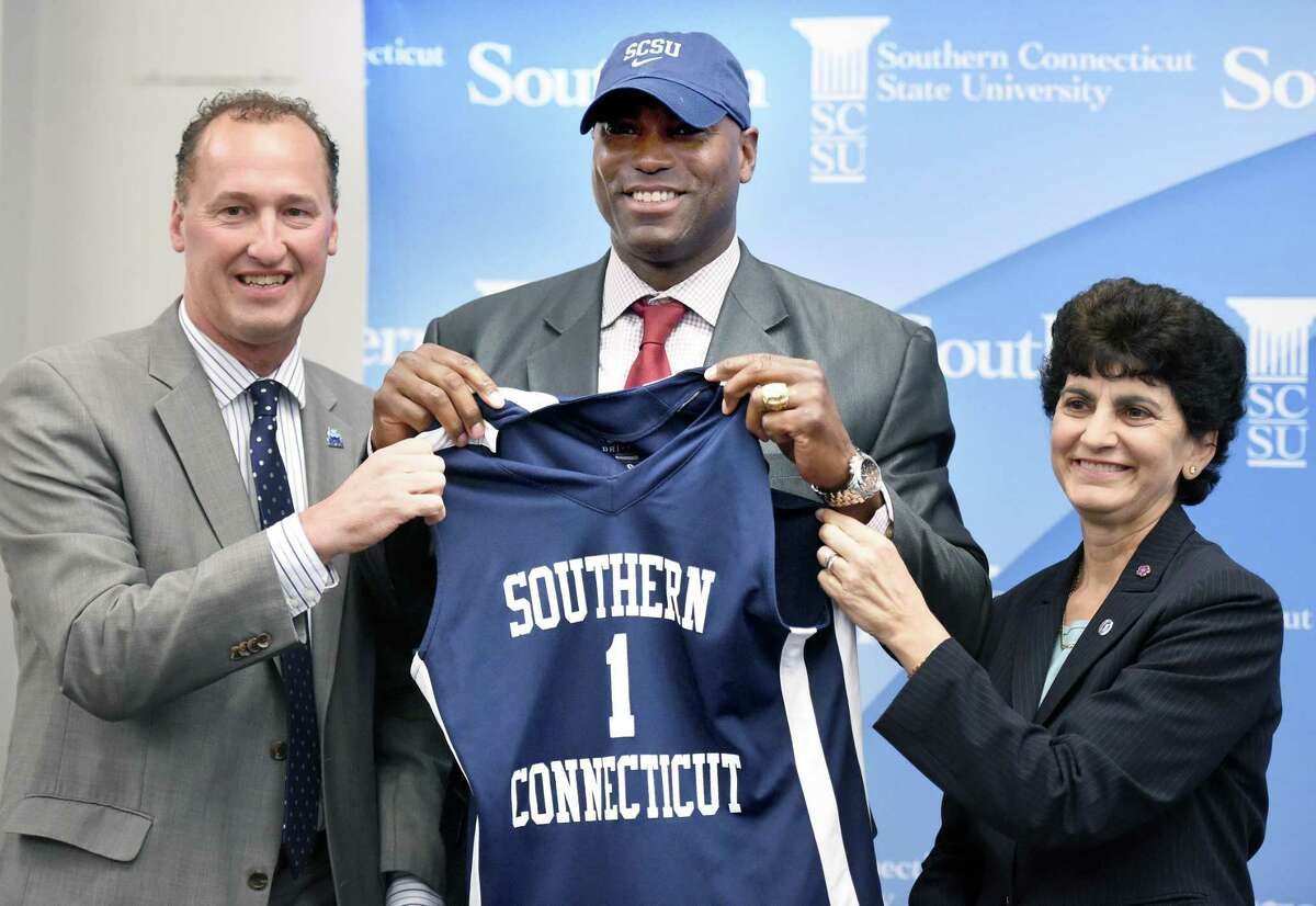 Scott Burrell, center, was named the new Southern Connecticut State University men's basketball coach in 2015. At left is athletic director Jay Moran and, at right, is Southern Connecticut State University President Mary Papazian.