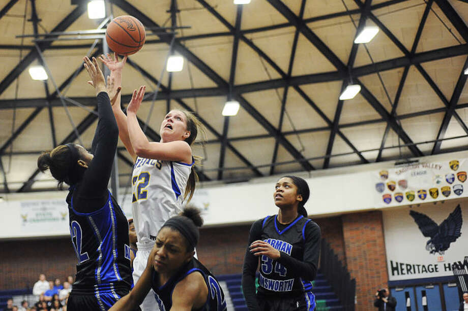 Midland High's Jessica Walter puts up a runner in traffic during a March 7, 2014 regional final against Flint Carman-Ainsworth. Photo: Daily News File Photo