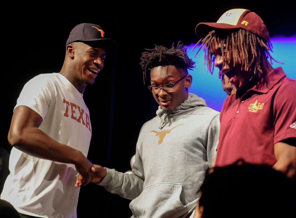 New Caney's Derrick Harris, Jr. (left) laughs beside Orian Wormley after signing to play football for the University of Texas during a signing ceremony at New Caney High School, Wednesday, Dec. 16, 2020, in New Caney.