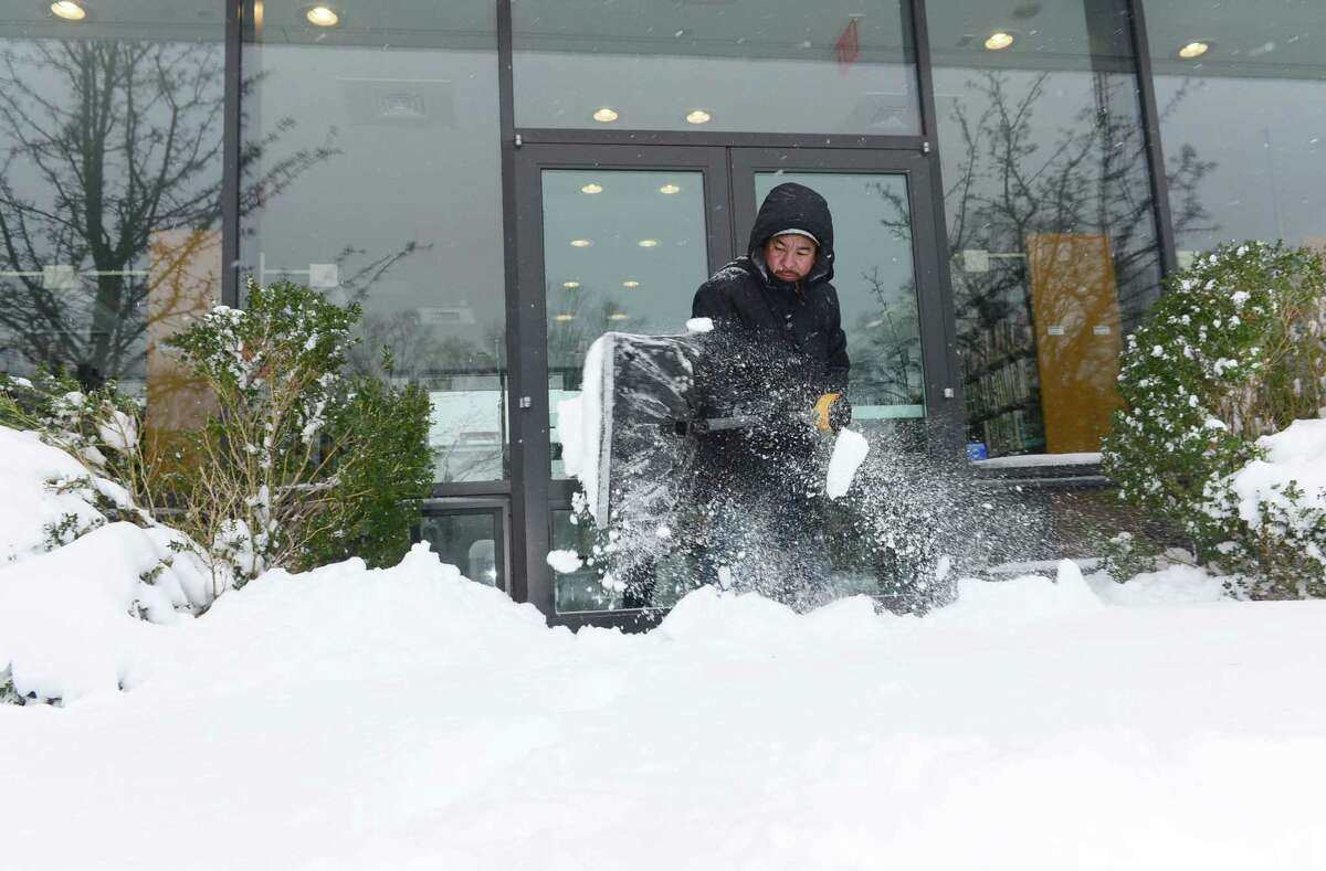 Wilton library employee Juan Carlos Olivares shovels snow from in front of the library during a previous snowstorm. The library is closing at 4 p.m. on Dec. 16 due to a coming storm.