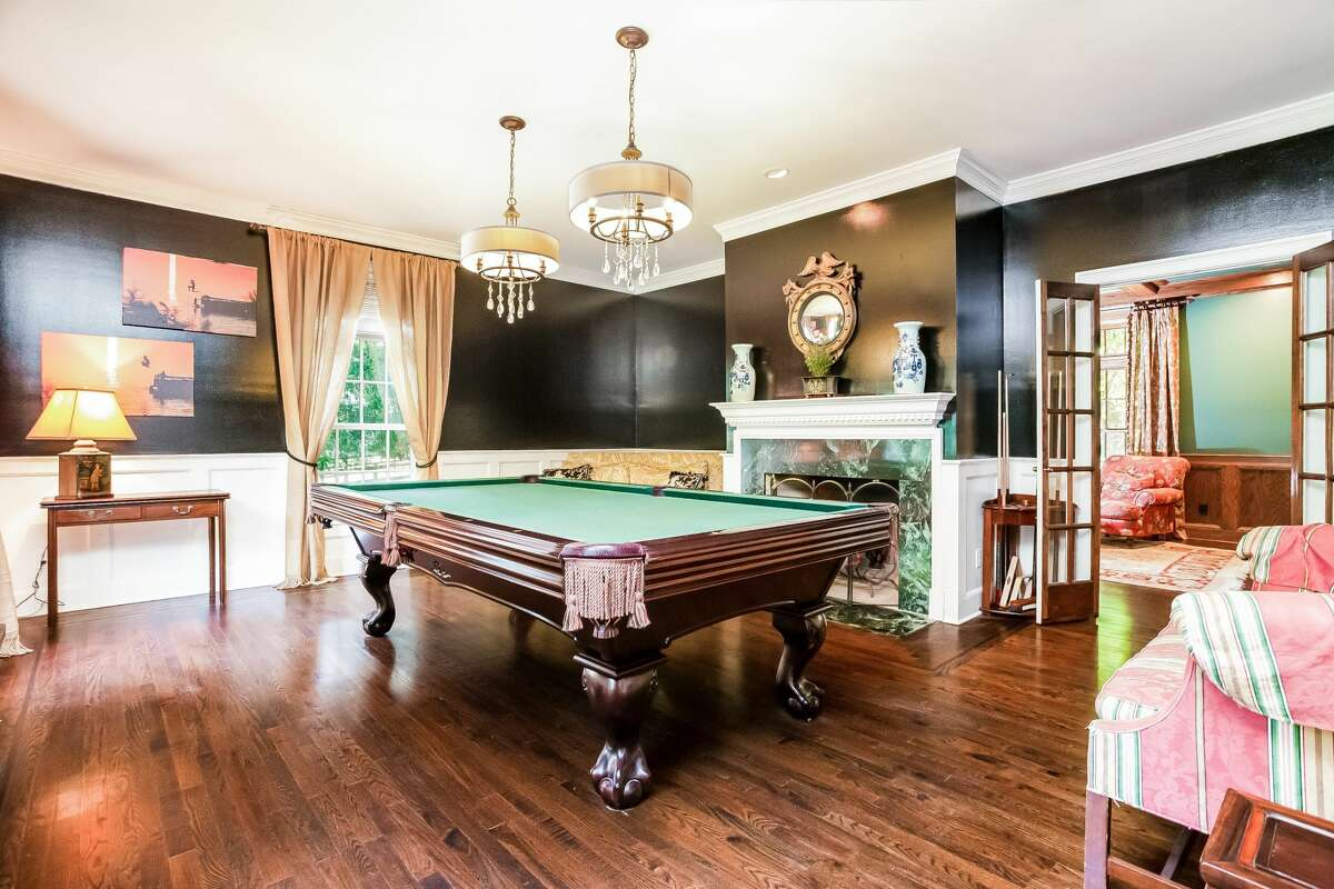 Formal living room with fireplace, converted into a game room at 801 Banks North Road, Fairfield.