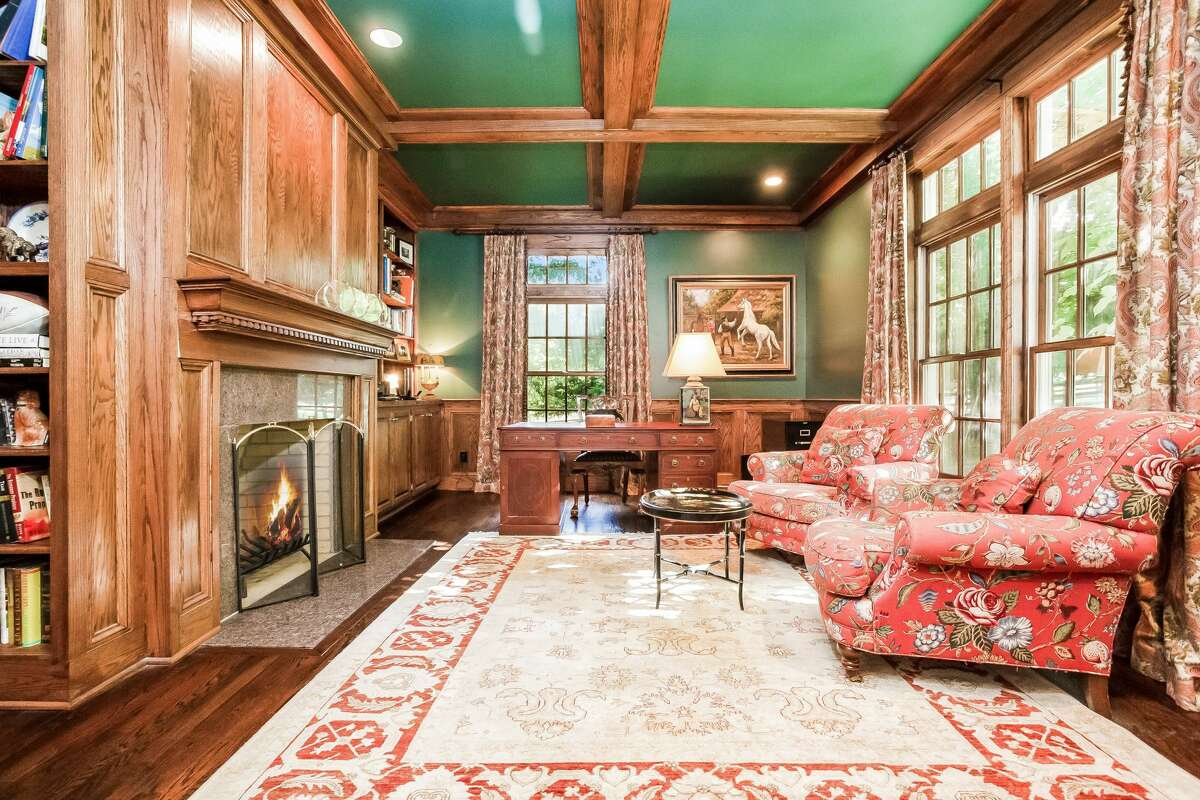 Office with fireplace and coffered ceiling at 801 Banks North Road, Fairfield. The door at the covered front entrance opens into a two-story foyer revealing 11 rooms and 6,083 square feet of living and entertaining space, including five bedrooms, four full and two half baths.
