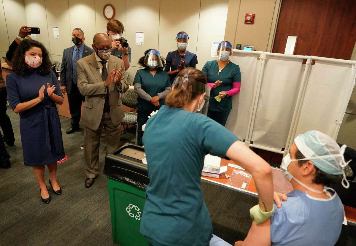 Harris County Judge Lina Hidalgo, left, Houston Mayor Sylvester Turner and others applaud after Houston Methodist Hospital RN Kristin Adolphs finishes giving Nestor Esnaola, surgical director of cancer center, his COVID-19 vaccination at Houston Methodist Hospital Tuesday, Dec. 15, 2020 in Houston.