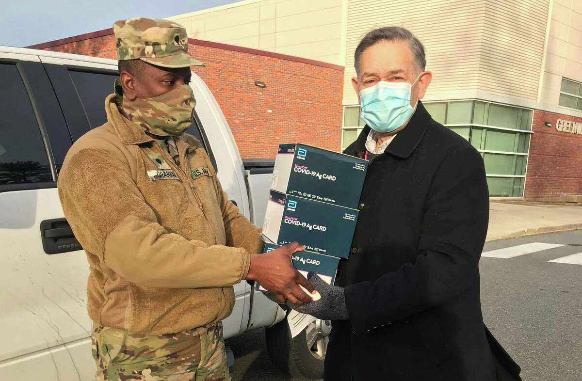 Greenwich High School Principal Ralph Mayo receives a shipment of Abbott BinaxNOW rapid antigen testing kits from National Guard Specialist Derriffee Graham, Dec. 16, 2020, in Greenwich, Conn.
