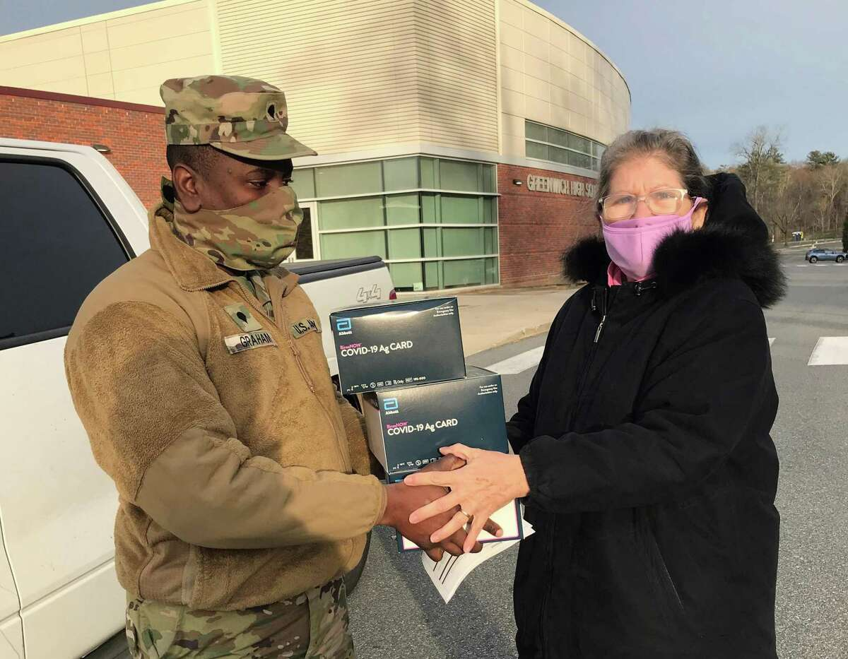 Greenwich Public Schools' Head of Nursing Mary Keller receives a shipment of Abbott BinaxNOW rapid antigen tests from from National Guard Specialist Derriffee Graham Dec. 16, 2020 in Greenwich, Conn.