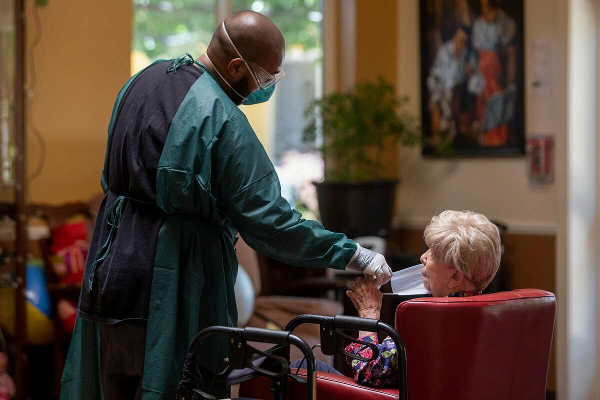 An employee helped a resident put on a surgical mask inside the recreation area at Gordon Manor assisted-care facility in Redwood City, Calif. in June.