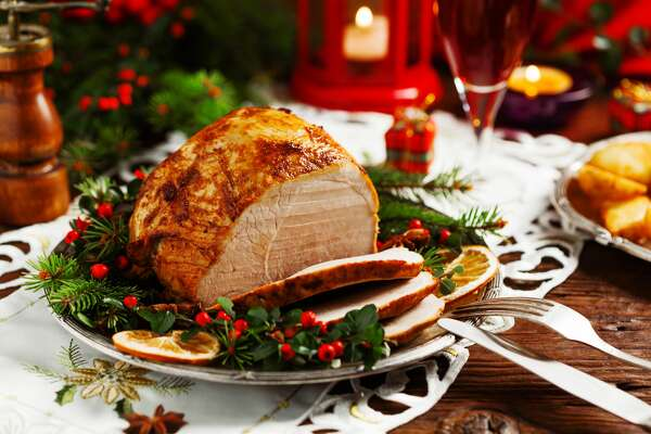 Christmas baked ham, served on the old plate. Spruce twigs all around. Front view.