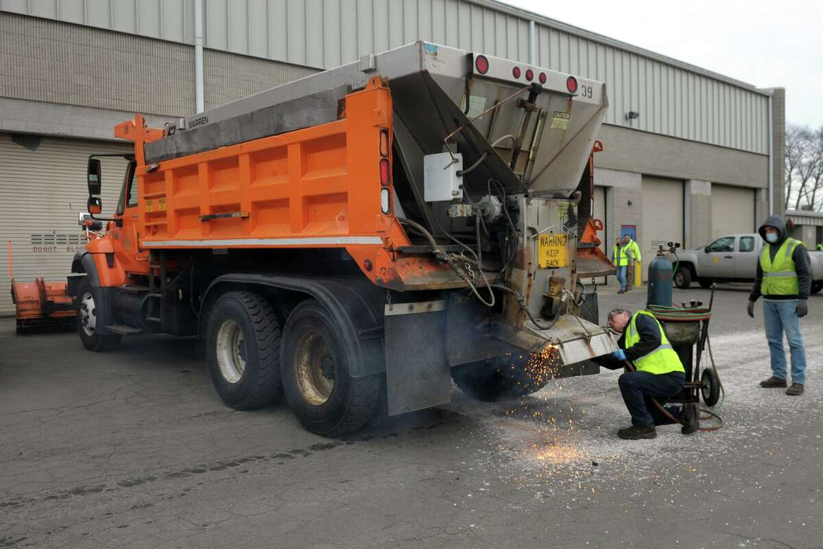 Rich Forest works to repair a salt spreader on the back of a truck outside the Town of Fairfield's department of public works garage, in Fairfield, Conn. Dec. 16, 2020.