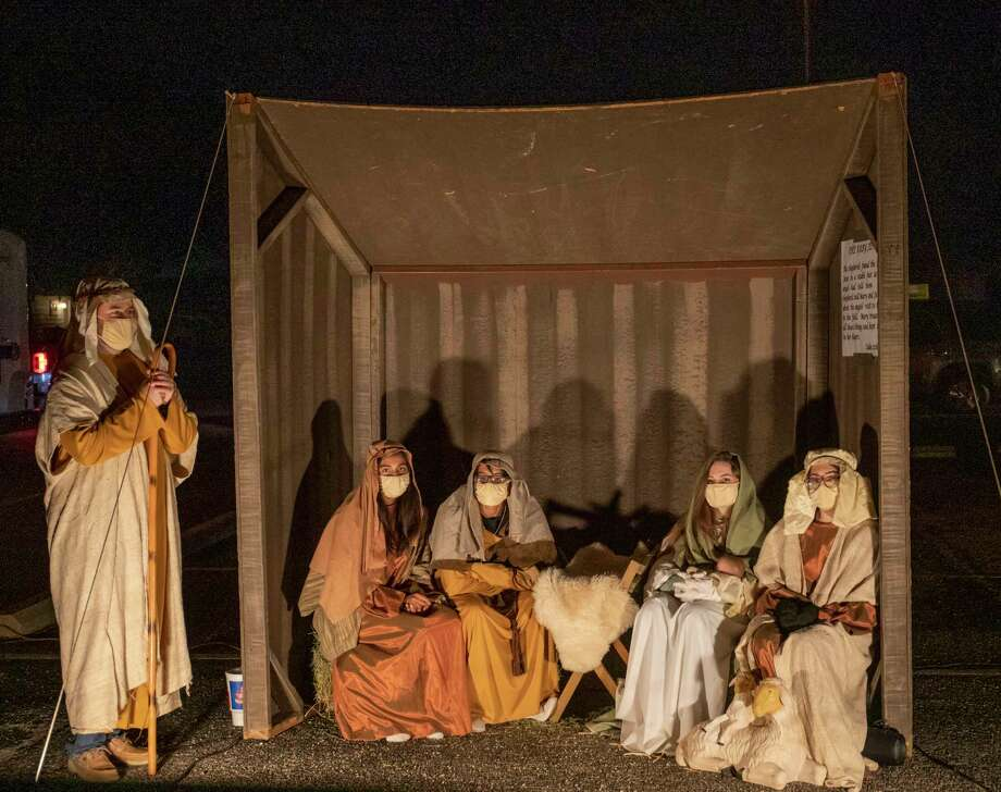 Hunter Kilborn(from left), LeeAnna Crudgington, Simon Crudgington, Kathe Hepfer and Annie Pendergrass sit in a manger during First Christian Church held a drive-thru event called Night in Bethlehem on Sunday, Dec. 13, 2020 at 1301 W. Louisiana Ave. Jacy Lewis/Reporter-Telegram Photo: Jacy Lewis/Reporter-Telegram