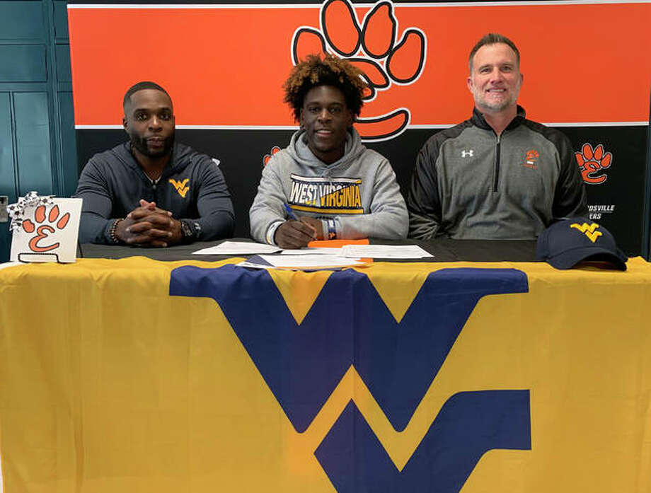 Edwardsville senior Justin Johnson, seated center, will play college football for West Virginia University. He is joined in the picture by his dad, left, and EHS coach Matt Martin.
