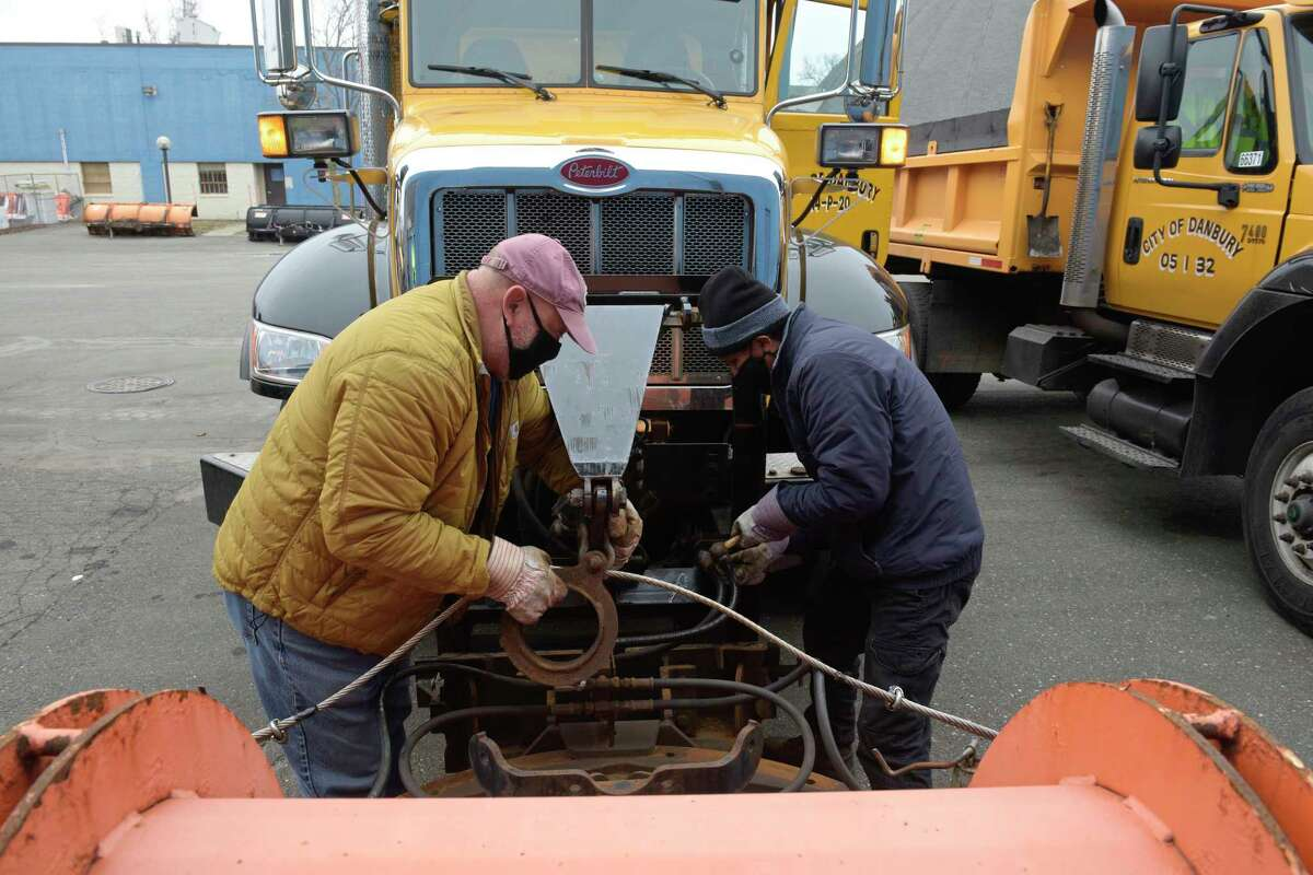 Don Eriquez, left, and Walter Garcia, install a plow on a truck at the city garage on Wednesday, December 16, 2020, in Danbury, Conn. in preparation for the forecast nor'easter.