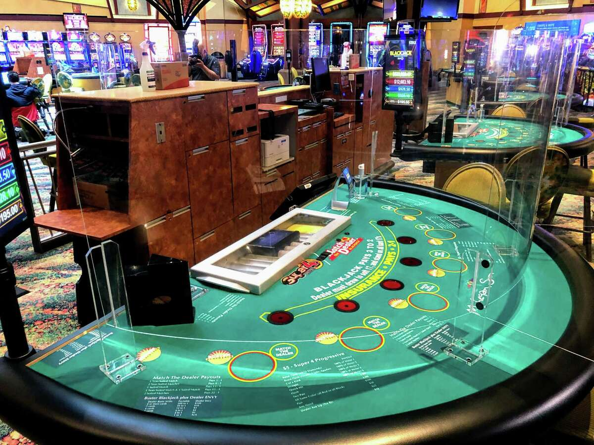 Plexiglass wraps around a blackjack table at Mohegan Sun in a preview of the casino's return in late spring.