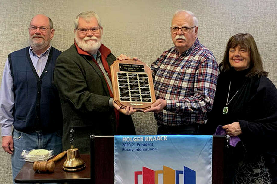 Jacksonville Sunrise Rotary President Jay Jamison (from left) and Paul Harris Fellowship Committee member Gordon Jumper present a Paul Harris Award to John Meece as Meece's wife, Linda, looks on.