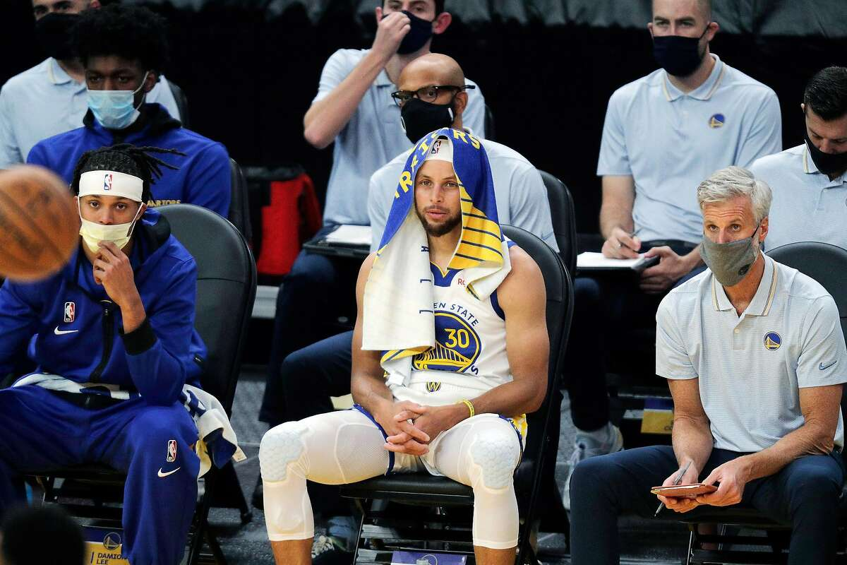 Damian Lee, left, Stephen Curry, center, andassistant coach Bruce Fraser take in a preseason game from the bench.