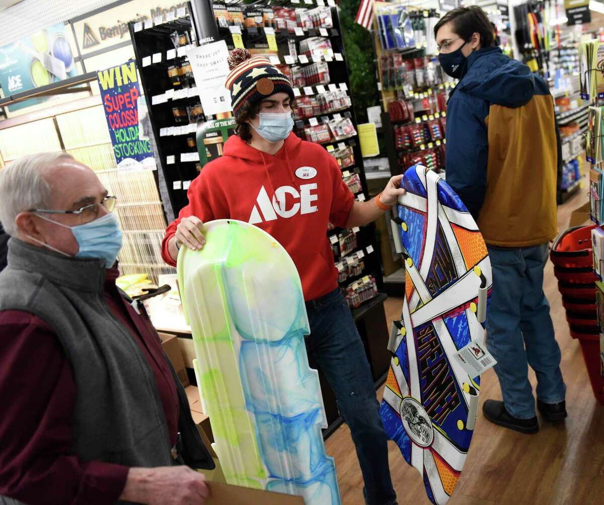 Store associate Chris Cosenza gets sleds for a customer at Feinsod Ace Hardware in Old Greenwich, Conn. Wednesday, Dec. 16, 2020. Folks stocked up on shovels, ice melt, and groceries in anticipation of the winter storm expected to dump more than a foot of snow starting Wednesday night.