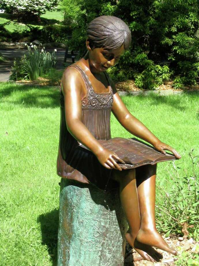 This cast bronze statue, depicting a girl reading poetry by Emily Dickinson, was stolen from Harvey Steadly's Tanglewood Lane property in Westport between Aug. 31 and Sept. 1. Photo: Contributed Photo / Westport News