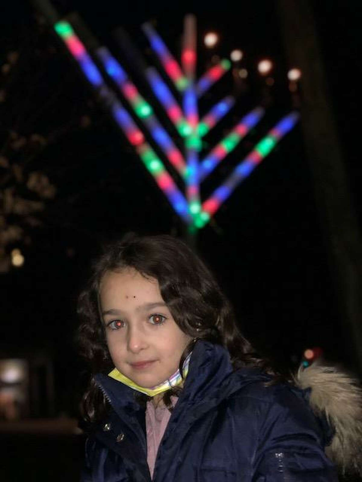 Chaya Deitsch at the menorah lighting presided over by her father, Rabbi Shalom Deitsch of Chabad Jewish Center of Ridgefield. The menorah, visible behind her, had four candles lit on Sunday, the fourth day of Chanukah.