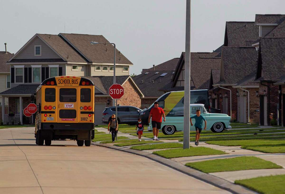 A bus drops off children in the Bay Colony Pointe West neighborhood, Thursday, Oct. 1, 2020, in League City. Homes in the neighborhood are exclusively for rent.