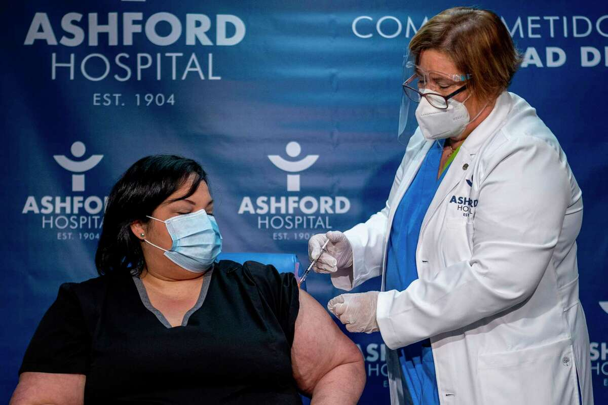 Yahaira Alicea, a respiratory therapist who treated the first two COVID-19 patients in Puerto Rico, gets her first shot of the Pfizer-BioNTech COVID-19 vaccine, administered by Epidemiologist Hilda Aleman, at the Ashford Medical Center in San Juan, Puerto Rico on Dec. 15, 2020. Alicea is the first Puerto Rican to get the vaccine in the island. (Ricardo Aruengo/AFP/Getty Images/TNS)