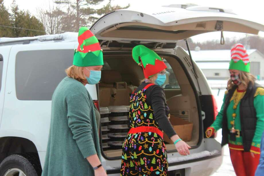 Volunteers and staff load holiday meals in the back of vehicles in order to deliver them to Frankort-Elberta Elementary Schools students. (Photo/Record Patriot)