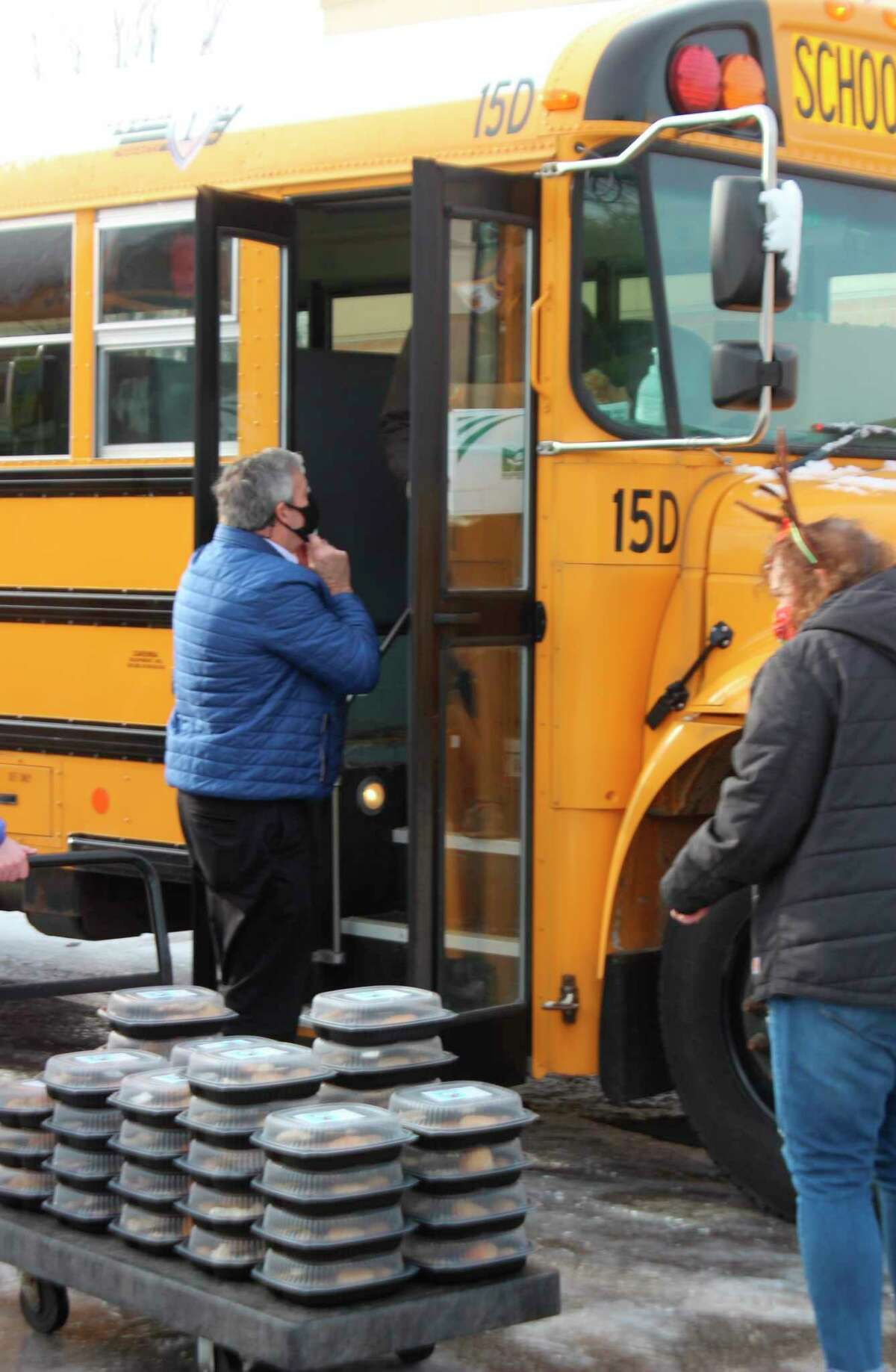 Volunteers and staff load holiday meals into a bus in order to deliver them to students. (Colin Merry/Record Patriot)