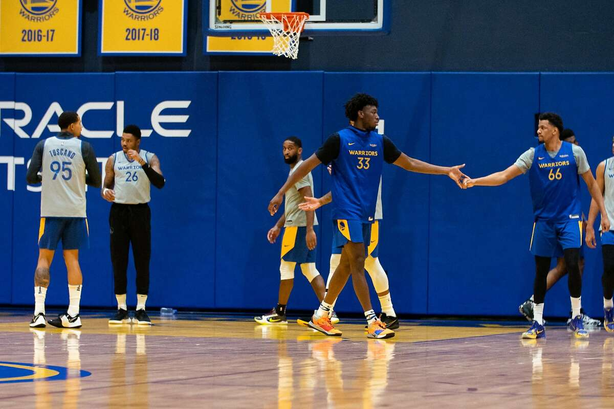 Golden State Warriors' James Wiseman (center) slaps hands with at Axel Toupane at practice at Chase Center in San Francisco, Calif. on Monday, Dec. 14, 2020.