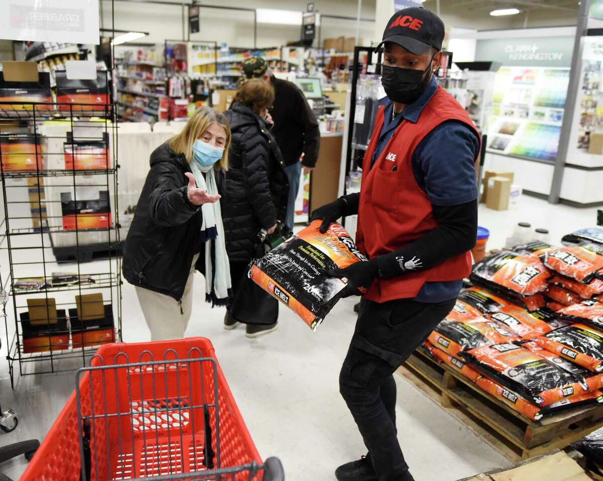Store associate Kadeem Mitchell loads ice melt into Shirley Ephrain's cart at Karp's Ace Hardware in Stamford on Wednesday. Folks stocked up on shovels, ice melt, and groceries in anticipation of the winter storm expected to dump more than a foot of snow starting Wednesday night.