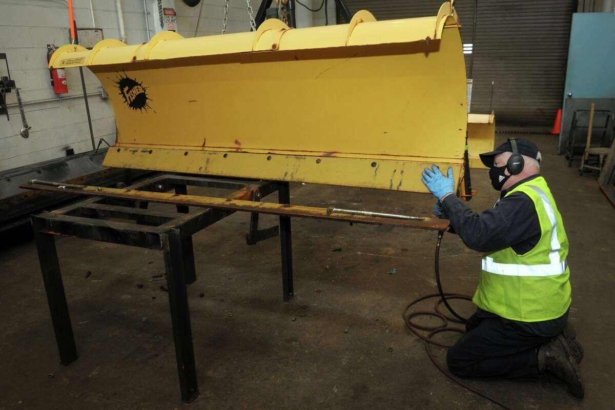 Sal Cicale works to prepare a snowplow with a new blade in the Town of Fairfield's department of public works garage, in Fairfield, Conn. Dec. 16, 2020.