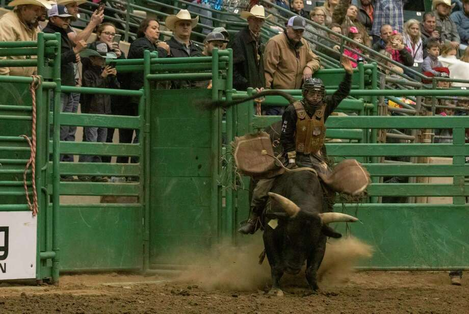 A bull rider tries to hold on to his bull during the Montgomery County Fair & Rodeo on Saturday, March 30, 2019 at Woodforest National Bank Arena in Conroe. The Montgomery County Fair Association plans to move forward with a full schedule at the 2021 fair and rodeo in April. Photo: Cody Bahn, Houston Chronicle / Staff Photographer / © 2018 Houston Chronicle