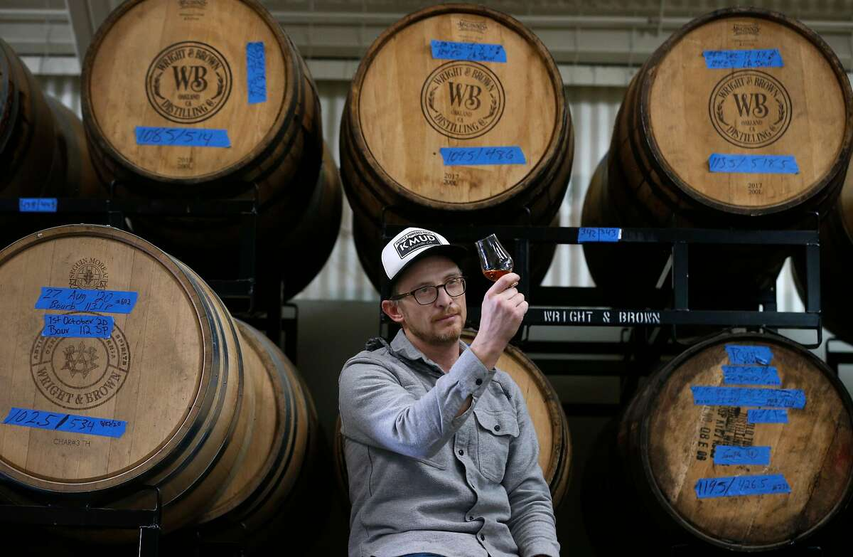 Earl Brown inspects whiskey aging in 200-liter barrels at Wright & Brown Distilling Co. in Oakland.