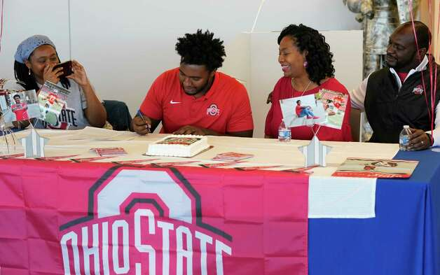 Rachel Jackson, left, takes a photo of her brother, Donovan Jackson, and their parents Melanie Jackson and Todd Jackson, right, as he signs with Ohio State at a signing event at Episcopal HS 4650 Bissonnet St., Wednesday, Dec. 16, 2020 in Bellaire. Photo: Melissa Phillip, Staff Photographer / © 2020 Houston Chronicle