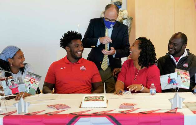Head Coach Steve Leisz, standing center, talks with Rachel Jackson, left, her brother, Donovan Jackson, and their parents Melanie Jackson and Todd Jackson, right, after Donovan signed with Ohio State at a signing event at Episcopal HS 4650 Bissonnet St., Wednesday, Dec. 16, 2020 in Bellaire. Photo: Melissa Phillip, Staff Photographer / © 2020 Houston Chronicle