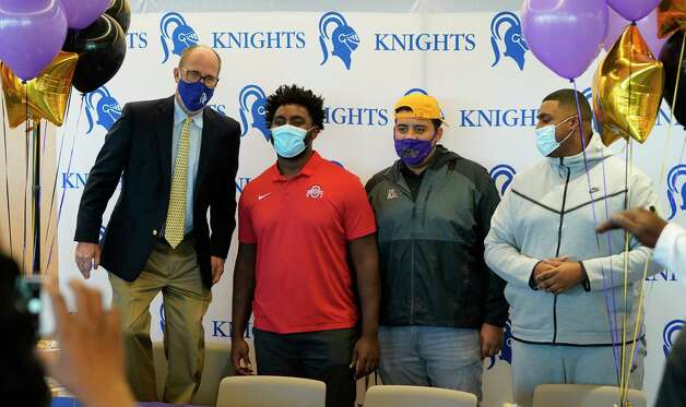 Head Coach Steve Leisz, left, jokingly stands on a chair as he poses with Donovan Jackson, Luis Chavarria and Cullen Montgomery, right, after a signing event at Episcopal HS 4650 Bissonnet St., Wednesday, Dec. 16, 2020 in Bellaire.  Donovan Jackson signed with Ohio State. Luis Chavarria signed with Prairie View. Cullen Montgomery signed with Oklahoma. Photo: Melissa Phillip, Staff Photographer / © 2020 Houston Chronicle