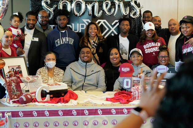 Cullen Montgomery, sitting center, poses with his aunt Patricia Williams, sitting left, his mother, Crystal Homes, brother Carson Montgomery, 9, grandmother, Willie Holmes, sitting right, and other family and friends during a signing event at Episcopal HS 4650 Bissonnet St., Wednesday, Dec. 16, 2020 in Bellaire.  Cullen Montgomery signed with Oklahoma. Photo: Melissa Phillip, Staff Photographer / © 2020 Houston Chronicle