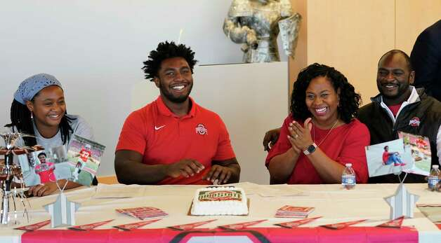 Rachel Jackson, left, poses with her brother, Donovan Jackson, and their parents Melanie Jackson and Todd Jackson, right, after he signed with Ohio State at a signing event at Episcopal HS 4650 Bissonnet St., Wednesday, Dec. 16, 2020 in Bellaire. Photo: Melissa Phillip, Staff Photographer / © 2020 Houston Chronicle