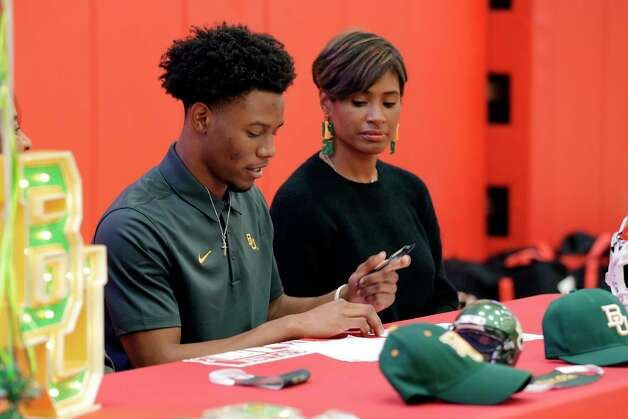 Cameron Bonner signs his contract for Baylor University as his mother NaKea Booner looks on during signing day ceremonies at the St. Thomas High School gymnasium Wednesday, Dec. 16, 2020 in Houston, TX. Photo: Michael Wyke, Contributor / © 2020 Houston Chronicle