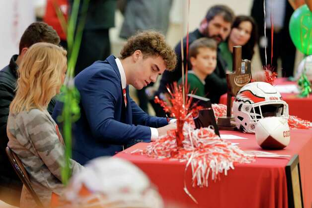 Maddox Kopp, center, signs his contract with Houston during signing day ceremonies at the St. Thomas High School gymnasium Wednesday, Dec. 16, 2020 in Houston, TX. Photo: Michael Wyke, Contributor / © 2020 Houston Chronicle