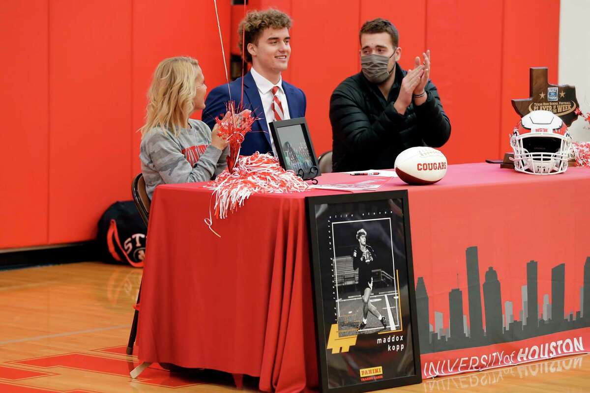 Maddox Kopp, center, flanked by his mother Deborah Kopp, left, and brother Braden Kopp is applauded after signing his contract with Houston during signing day ceremonies at the St. Thomas High School gymnasium Wednesday, Dec. 16, 2020 in Houston, TX.