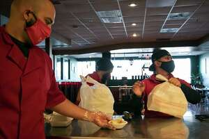 Hesham Werfelli puts out an order of hummus for a dine-in customer as servers Marco Olivares, center, and Brandon Ramirez pack up to-go orders at Tripoli's.