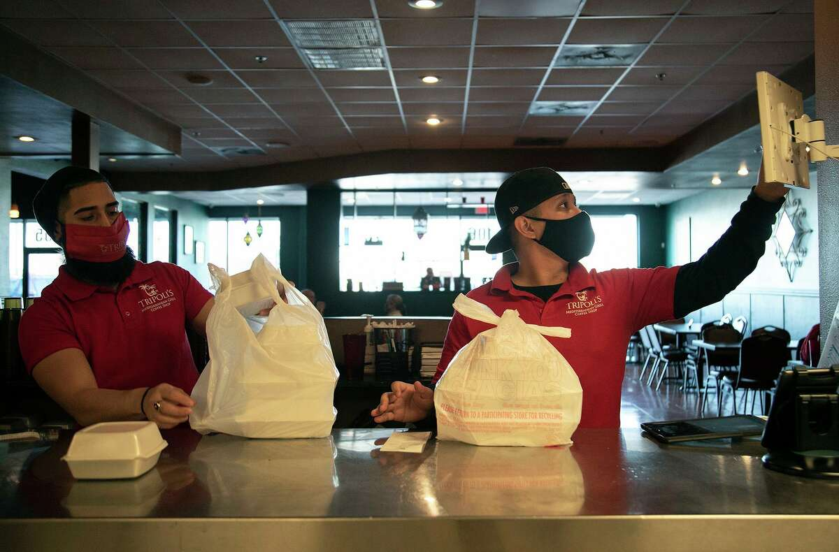 Servers Marco Olivares, left, and Brandon Ramirez pack up to-go orders at Tripoli's.