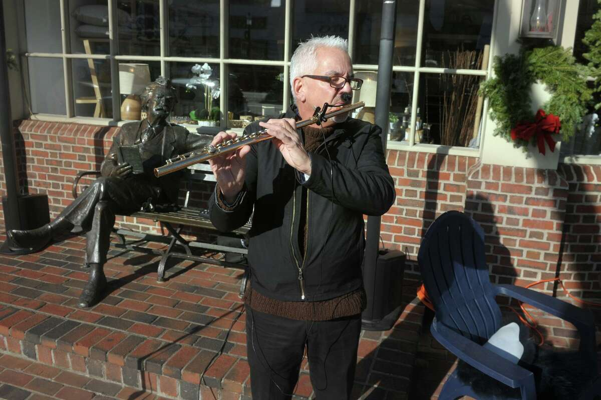 As the permanent sculpture of Mark Twain looks on, Jim Magrath plays holiday songs on flute in front of KL & Sam during Shop & Stroll day along the Boston Post Rd., in Fairfield, Conn. Dec. 3, 2020.