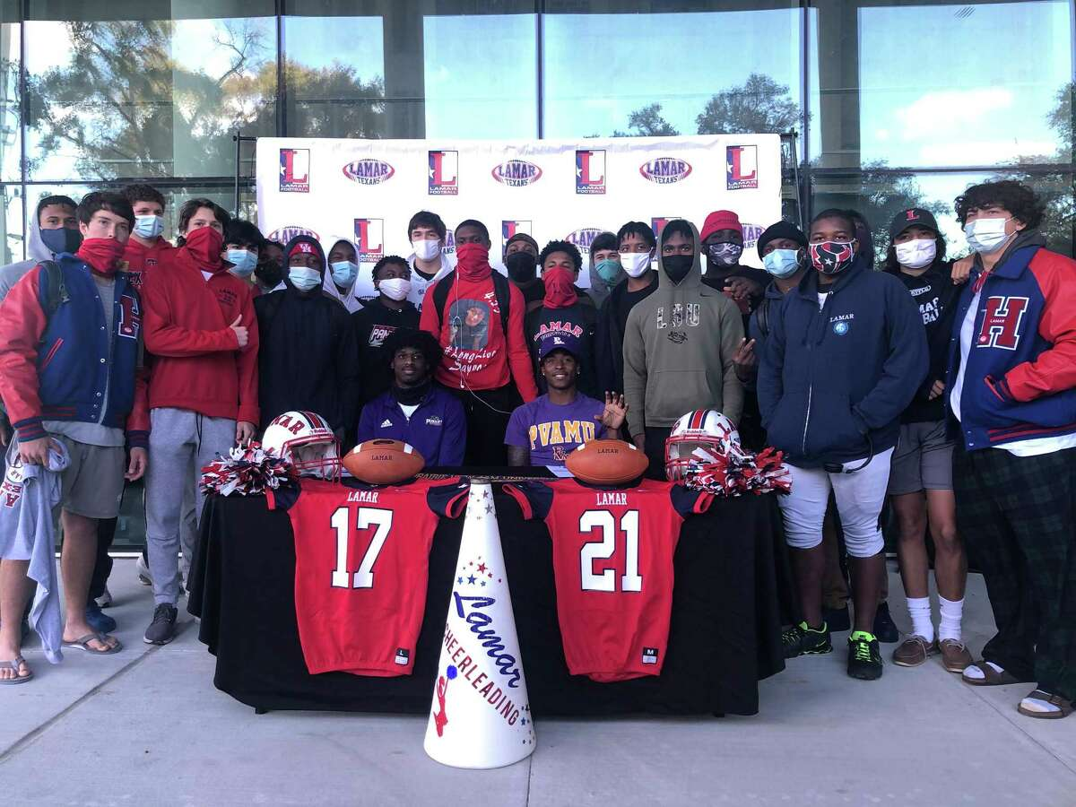 Lamar's Khai'mon Samuel (right) and Lamont Landry (left) pose for a photo surrounded by their teammates after they sign their National Letters of Intent accepting athletic scholarships to play football at Prairie View A&M University during a ceremony at the school on the afternoon of Dec. 16