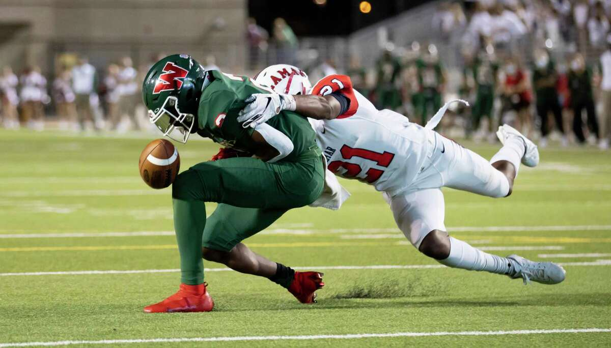 The Woodlands wide receiver Teddy Knox (2) gets tackled by Lamar cornerback Khai'mon Samuel (21) during the second quarter of a non-district game at Woodforest Bank Stadium in Shanendoah, Friday, Oct. 2, 2020.