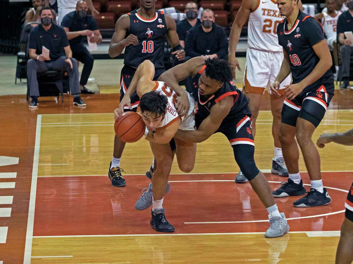 Texas forward Brock Cunningham, left, fights for possession with Sam Houston State forward Trista Ikpe, right, during the second half of an NCAA college basketball game, Wednesday, Dec. 16, 2020, in Austin, Texas. Texas won 79-63. (AP Photo/Michael Thomas)