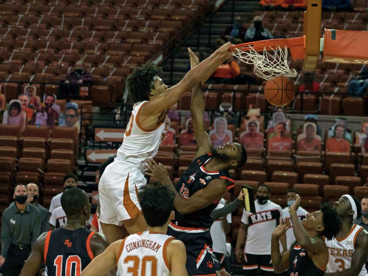 Texas forward Jericho Sims, left, dunks the ball against Sam Houston State forward Dylan Robertson, right, during the first half of an NCAA college basketball game, Wednesday, Dec. 16, 2020, in Austin, Texas. (AP Photo/Michael Thomas)