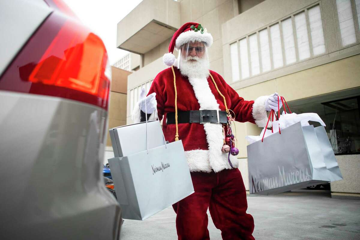 Curbside Santa, known as Michael Gee when in civilian clothes, delivers packages directly to customers' cars in the valet parking area at Neiman Marcus in the Galleria.