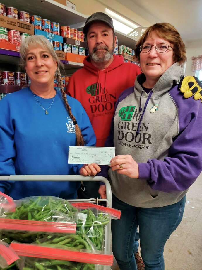 Bread of Life Food Pantry director Lynne Mills (far left) is presented with a donation check for $750 from Steve and Audrey Dominque, owners of The Green Door Baldwin Provisioning Center. (Submitted photo)