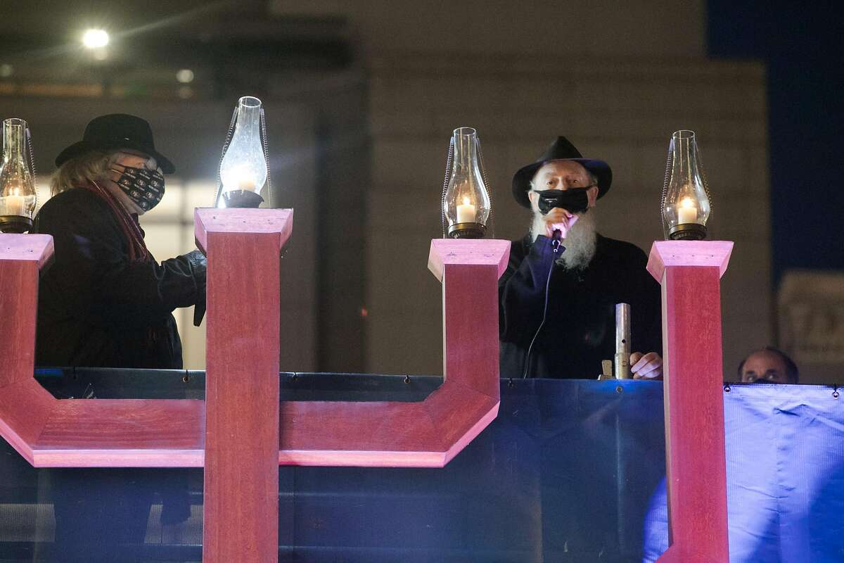 Chabad of San Francisco Rabbi Yosef Langer, right, speaks after lighting the menorah in Union Square while Brian Webster holds a cellphone with a light to broadcast the event online, in San Francisco on Dec. 16, 2020. It is the 45th consecutive year the menorah has been lit in Union Square.
