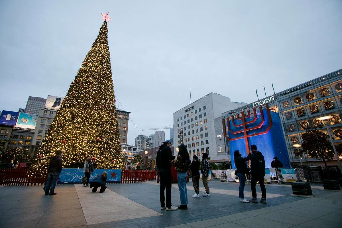 People gather to to take photos in front of the Macy's holiday tree and the Bill Graham Menorah in Union Square in San Francisco on Dec. 16, 2020.
